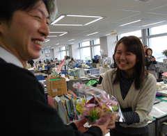 男性職員から花を贈られる女性職員=県庁