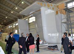 仮組立工場で、完成したナセルカバーの前側部分を見学する関係者ら=北茨城市磯原町上相田