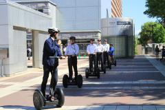G7開幕を間近に控え、市職員(手前左)からセグウェイ操縦の指導を受ける警備会社の社員=つくば市吾妻
