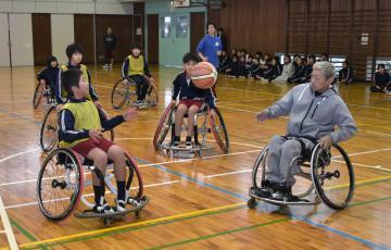 車いすバスケットボールを体験する鉾田市立旭東小の児童たち。右は指導する斎藤信之さん=鉾田市荒地