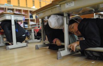 防災訓練で机の下に身を隠す児童=水戸市西原