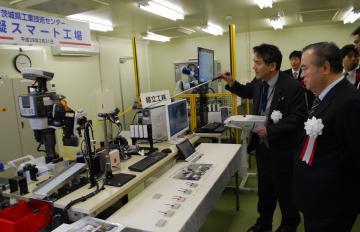 完成した模擬スマート工場でロボットを視察する橋本昌知事と関係者=茨城町長岡