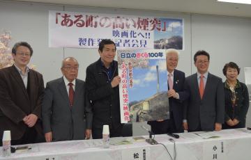 「ある町の高い煙突」の映画化を発表する松村克弥監督(左から3人目)と日立市の小川春樹市長(同4人目)など関係者=日立市幸町