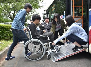 車椅子でバスの乗降体験する学生たち=水戸市文京