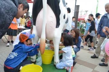 疑似乳搾り体験を楽しむ子どもたち=小美玉市山野の「空のえき そ・ら・ら」