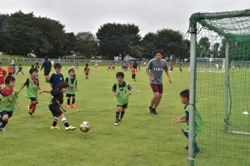 サッカー教室で中田浩二さんとプレーする子どもたち=結城市鹿窪