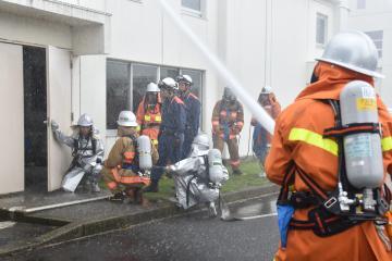 放水活動とともに要救助者の救出に向かう参加者=茨城町長岡の県立消防学校