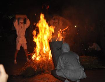 白装束姿の若者が燃え上がった炎を畳をたたきつけ風圧で消火すると見物人から歓声が上がった=下妻市の大宝八幡宮