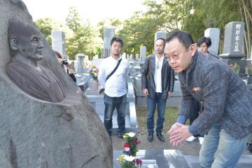 平塚八兵衛の墓前に立ち、人柄などをしのぶ近藤芳正さんら=土浦市
