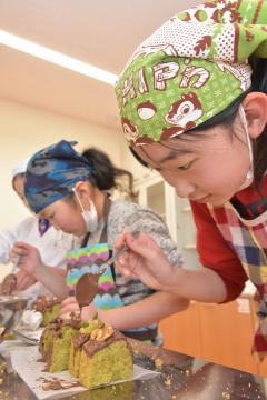 パウンドケーキにチョコレートをかける児童=地域交流センターともべ