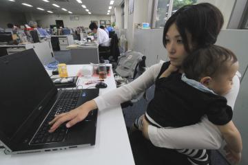 「子連れ出勤モデル事業」のテスト導入で、子どもを抱えて仕事に励む東京フード総務課の宮越七奈さん=つくば市上大島