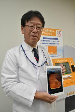 内視鏡の検査画像が表示されたタブレットを手にする友愛記念病院の加藤奨一院長=古河市東牛谷