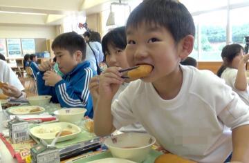 給食に提供されたロシア料理のピロシキを頬張る児童=鹿嶋市中の市立中野西小