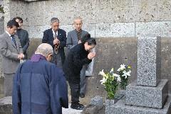 波山の墓前で手を合わせる茨城工芸会の会員=筑西市乙の妙西寺