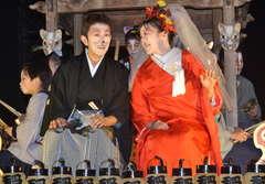 狐の嫁入りパレードで沿道の声援に応える神長真一さん(左)とめぐみさん=笠間市笠間