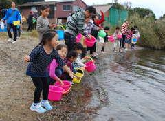 シジミの稚貝100万匹を放流する親子連れ=茨城町の涸沼湖畔
