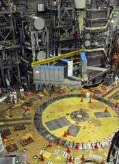 JT-60SAの組み立てが始まり、クレーンでつり下げられ設置される基礎部分=那珂市向山の那珂核融合研究所