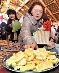 出品者自慢の揚げ餅を試食する参加者=稲敷市上君山のポティロンの森