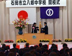 開校式で久保田健一郎市長から校旗を受け取る古谷田明良校長(左)=石岡市柿岡