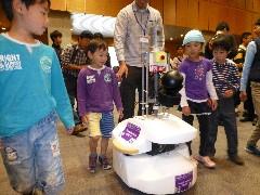 自律走行するロボットに付いて歩く子どもたち=つくば市竹園