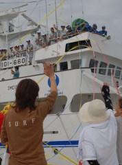 出港する実習船「鹿島丸」と互いに手を振る実習生と家族たち=茨城港大洗港区