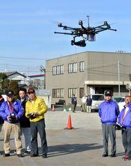坂東市職員の前で、災害対策として導入された無線操縦ヘリコプターの実演飛行が坂東ラジコンクラブ会員らによって行われた=坂東市岩井