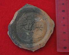 「〓(ひるくながひ)」という国字が刻まれた土器の底面の破片。隣に「女」の字も刻まれている