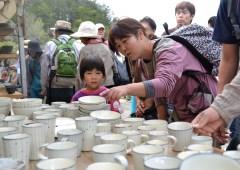 「笠間の陶炎祭」会場に並んだ焼き物を眺める来場者=笠間市笠間