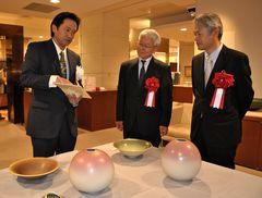 個展の来賓者に作品を解説する井上英基さん(左)=水戸市泉町の京成百貨店