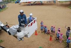 地上で園児らが見守る中、高所作業車を体験する年長組園児=鉾田市野友の串挽保育園