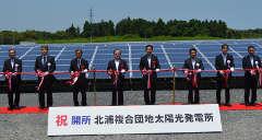 「北浦複合団地太陽光発電所」の開所をテープカットで祝う関係者ら=行方市内宿