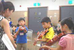 バイオリンに初挑戦する子どもたち=日立市幸町