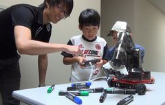 ロボット操作を体験する参加者=那珂市菅谷