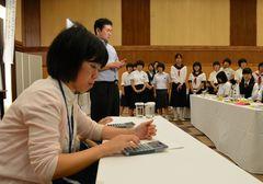 県立鬼怒商高の教諭や生徒が披露する電卓さばきを、興味を持って見詰める中学生たち=筑西市玉戸