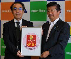那珂市特産品ブランドの認証ロゴマークとデザインした大和田幸一さん(左)、海野徹市長=同市役所