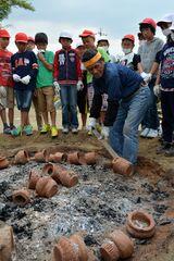 焼き上がった縄文土器の取り出し作業を見守る児童たち=筑西市立竹島小