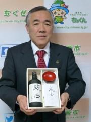 筑西市誕生10周年記念酒と酒器セットの第1号品を贈られた須藤茂市長=同市役所