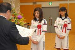表彰を受ける青木梨沙さん(中央)と藤井志保さん=県庁
