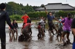 泥だらけになりながらバレーを楽しむ大学生や子どもたち=筑西市倉持