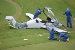 つくばねカントリークラブに墜落した超軽量飛行機を調べる警察官=16日午前9時50分ごろ、つくば市神郡