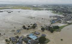 台風18号の影響による大雨で鬼怒川(右下)が氾濫し、決壊した堤防から流れ出す水=10日午後1時25分、常総市(共同通信社ヘリから)