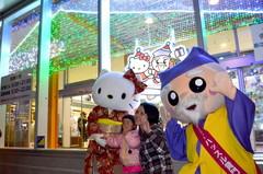 ハローキティとハッスル黄門を両脇に記念撮影する空港利用客=小美玉市与沢