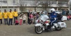 「スクールガード河間」10周年記念イベントで走行披露する県警白バイ隊=筑西市立河間小