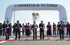 テープカットで筑西幹線道路の開通を祝う橋本昌知事や須藤茂市長ら=筑西市東榎生
