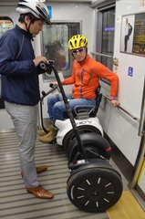 電車内の優先席付近で実験中の移動ロボットのセグウェイ(手前)とジェニー(奥)