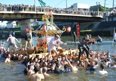 大勢の観衆が見守る中、勇壮に行われた下館祇園まつりの川渡御=7月31日午前7時42分、筑西市の勤行川大橋下流