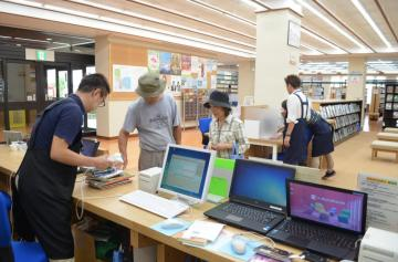 再開した常総市立図書館で本を借りる市民=同市水海道天満町