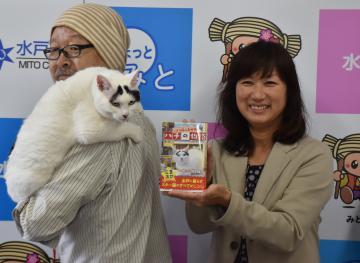 飼い主の前田陽一さん(左)に担がれる「ハチ」と、糸久たばこ店の長谷川香店長=水戸市役所南側臨時庁舎