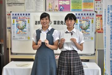 自分宛ての選挙メッセージはがきを手にする久保田真央さんと斎藤留菜さん(左から)=水戸市三の丸
