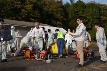 車両消毒に使用する「動力噴霧器」を体験する参加者ら=水戸市上国井町